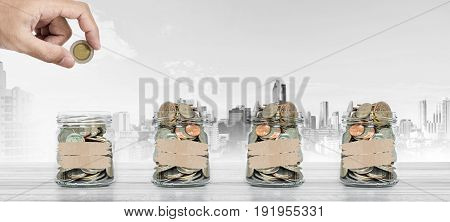 Money saving, Hand putting coin in glass jar with coins inside, with city background