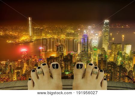 Barefoot girl on top of a building thinking of suicide, Victoria Harbor, skyscrapers and Hong Kong skyline at night. Depression and stress urban life concept.