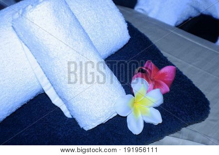 Massage table with rolls of white towels and plumeria flowers Close up of a massage table with white rolled towels, blue spread towel and decorated with red and white plumeria flowers in a spa