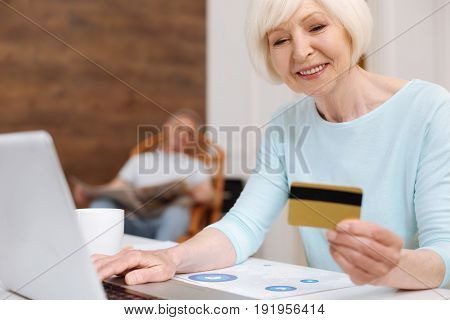 Convenient technologies. Beautiful productive enthusiastic lady using her laptop for purchasing things and paying for them with her credit card