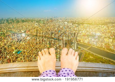 Barefoot girl on top of a building thinking of suicide, over Tokyo cityscape with Sumida River Bridges at sunset. View from high Japan skyscraper. Depression and stress urban life concept.