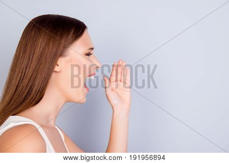 Hey! Cheerful Young Lady In White Casual Singlet Is Shouting And Holding Hand Near Her Open Mouth On