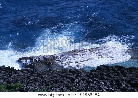 Coral platform with gentle waves  A beautiful coral platform and rock formations complete with gentle foaming waves in the seashore
