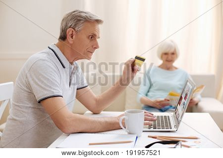 Looking for best option. Dedicated intelligent elderly gentleman searching for suitable item and buying it from an online store while paying with his credit card