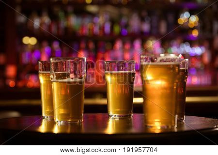 Glasses of cold fresh white light beer on the wooden bar counter in the pub