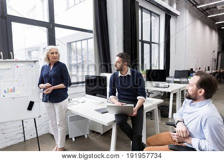 Mature business woman making a presentation for her colleagues at whiteboard