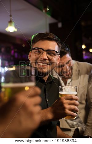 Smiling young man having beer with his friends at a pub