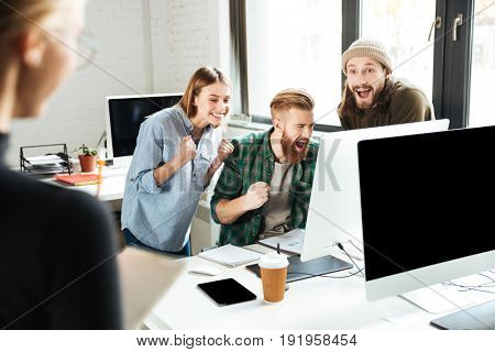 Image of young smiling colleagues in office talking with each other using computer. Looking aside make winner gesture.