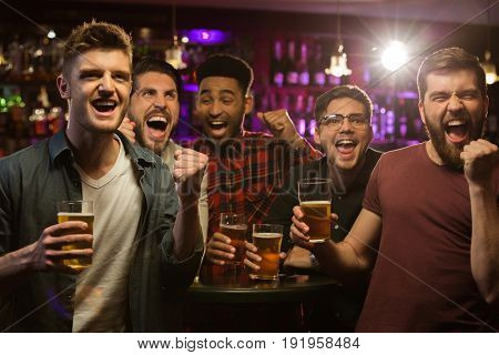 Four happy men holding beer mugs and gesturing while watching TV in bar or pub