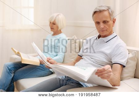Focused reader. Nice focused elderly man sitting in a living room and enjoying morning newspaper while his wife reading a book