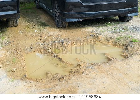 Wheel track in mire or car mired rut fragment mired in mud in car park.