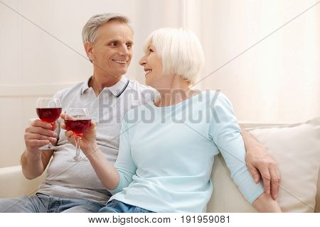 Young at heart. Romantic loving attracted couple spending weekend at home and sharing a romantic moment while having some wine