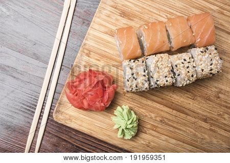 Sushi rolls with salmon and black and white sesame seeds ginger wasabi and sushi sticks lie on a light wooden plank on a dark brown background