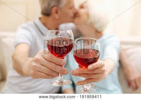 Forever together. Sweet caring emotional family having a nice time together while kissing and drinking some wine