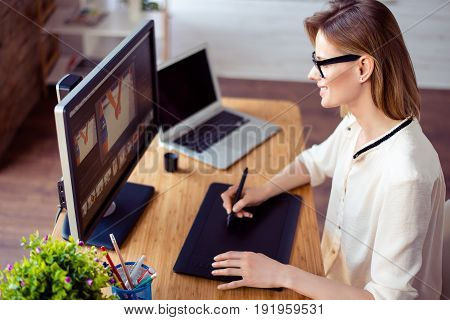 Young Professional Retoucher Sitting At The Table At Home And Working With Graphic Digital Tablet