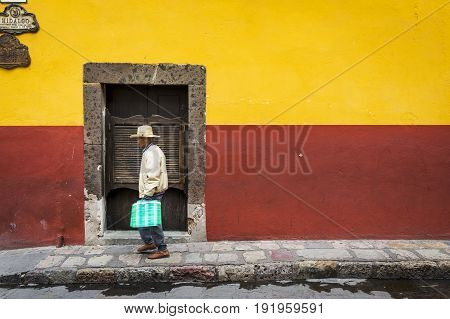 San Miguel de Allende Mexico - May 29 2014: Man passing in front of a door in the historic center of the city of San Miguel de Allende Mexico.