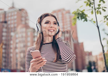 Carefree Young Lady Is Listening To Favourite Song On Her Smartphone Outdoors, Walking On The Spring