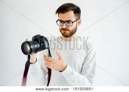 Portrait of a thinking male photographer with digital camera