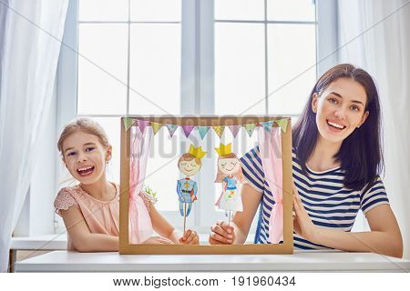 Happy loving family. Mother and her daughter in kids room. Funny mom and lovely child having fun and playing performance in the puppet theater indoors. Prince and princess.