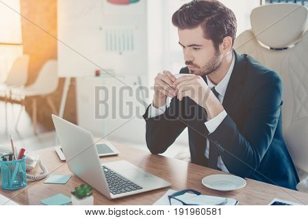Young Man Is Concentrated On Reading His Email While Drinking Coffee In Office. He Is In Formal Wear