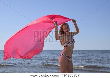 Blond Girl In A Bikini Standing On The Beach And Holding A Red Silk Handkerchief. Beautiful Young Wo