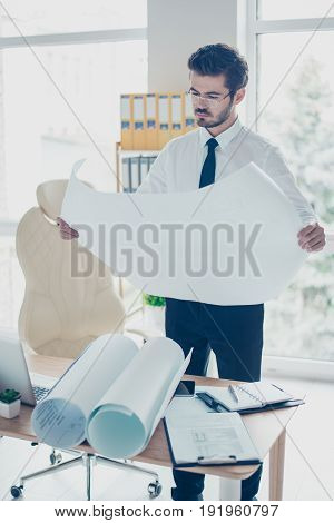 Vertical Photo Of Concentrated Worker In Formal Suit And Spectacles Looking At Blueprint In His Hand