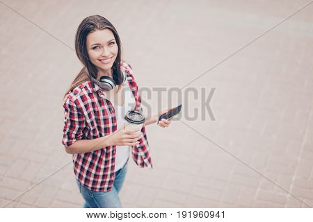 Top View Of Dreamy Young Female Student, Who Is Having A Tea And Walking In The City Outdoors, Smili
