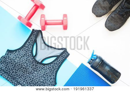 Creative flat lay of sport equipments with sport clothing on white and blue background
