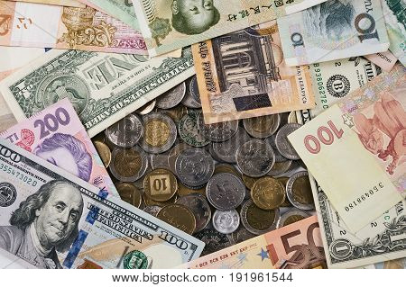 Coins and banknotes money from different countries: dollars euros hryvnia rubles cash.