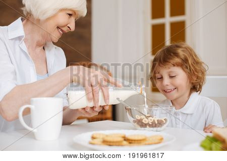 Is this enough. Bright positive careful grandma pouring milk in a bowl while making breakfast for his grandson who loving sweet things
