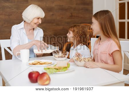 Would you like some milk. Active bright positive family gathering at the table for eating breakfast while grandma poring fresh milk in their bowls