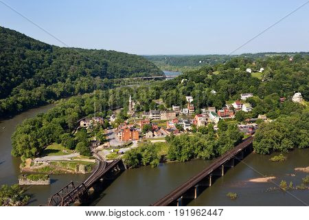Aerial view of the town of Harpers Ferry West Virginia which includes Harpers Ferry National Historical Park located between the Potomac River and the Shenandoah River. Traffic can be seen moving along the bridge in the distance.