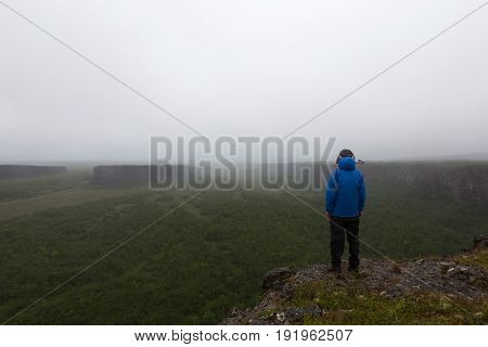 Solitude Landscape In Iceland Mist. Single Male Traveler Standing On The Cliff Of Famous Horseshoe N