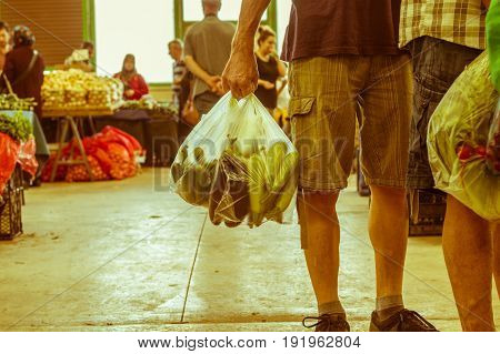 Man Holding Plastic Shopping Bag With Vegetables In A Typical Turkish Greengrocery Bazaar