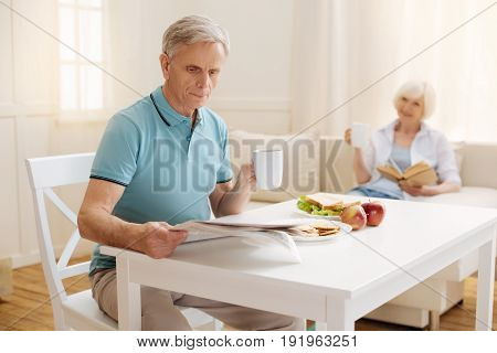Busy from the start. Intelligent focused elderly man reading a newspaper while holding a cup of coffee and eating his healthy breakfast with his wife