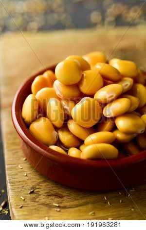 closeup of an earthenware bowl full of altramuces, lupinus albus beans traditionally eaten as snack in Spain, and also in Portugal and Italy, where are known as lupini and tremocos, respectively