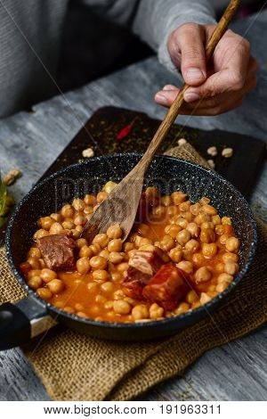 closeup of a young caucasian man stirring with a wooden spoon a frying pan with spanish cocido madrileno, a stew typical of madrid with chickpeas, pork, bacon, chorizo and ham, on a wooden table