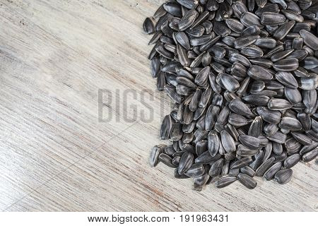 Black sunflower seeds lie on a light wooden background in the right side of the frame