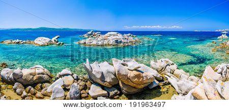Granite rocks in sea, amazing azure water, white sailboats in background near Porto Pollo, Sardinia, Italy. Banner