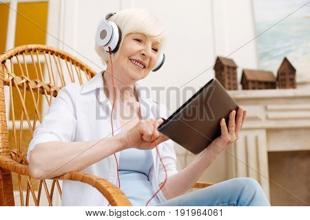 Choosing songs. Talented inspired clever lady wearing headphones and searching for new songs while creating a perfect playlist