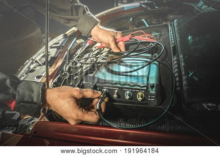 car diagnostic: hands of electrician connect the oscilloscope to the engine