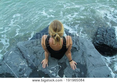 stylish outdoor woman alone sitting on stone coast and looking at sea
