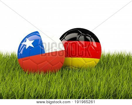 Two Footballs With Flags Of Chile And Germany On Green Grass