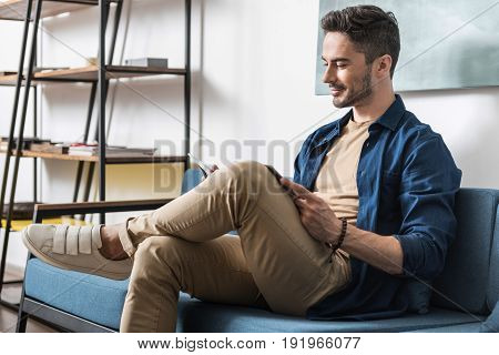 Profile of young jolly man with beard reading journal and smiling. He is sitting on cozy couch with one leg laying on knee