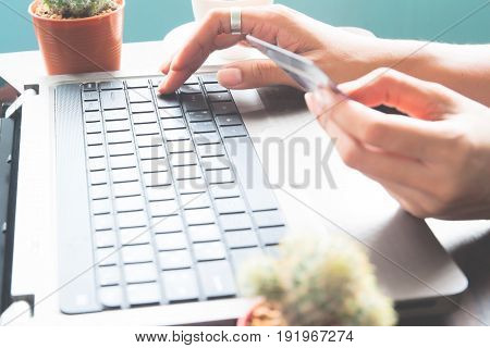 Woman press the enter button on laptop keyboard and using credit card Online shopping
