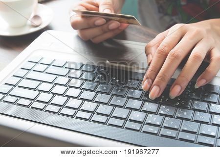 Female hands using laptop and credit card Online shopping and financial concept