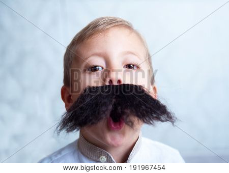 A little boy with a mustache, wants to be an adult