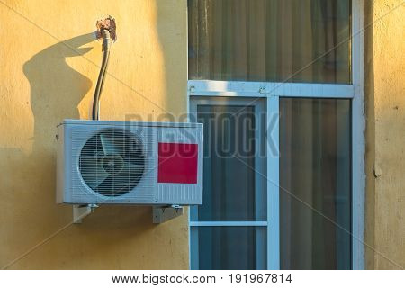 The window and the air conditioner on the facade of a apartment building