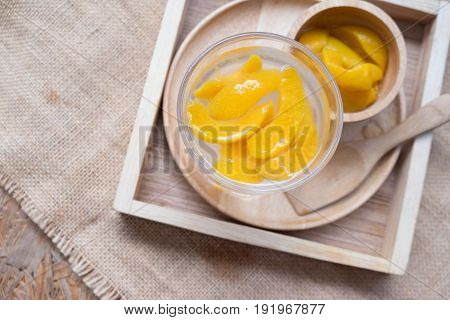 Fresh sparkling beverage with slice peaches on wooden tray