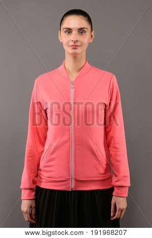 Young hipster girl wearing blank pink cotton zip up sweatshirt with copy space for your design or logo mock-up of ltemplate womens hoodie grey wall in the background